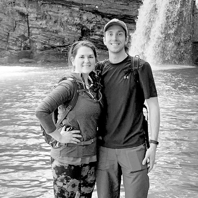 Hayley Knowles and Robert McGougan hiking by a waterfall on a camping trip