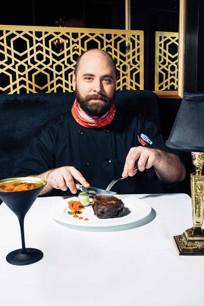 Chef de Cuisine Michael Quinn at Bridgeman's Chophouse eating dry-aged delmonico steak