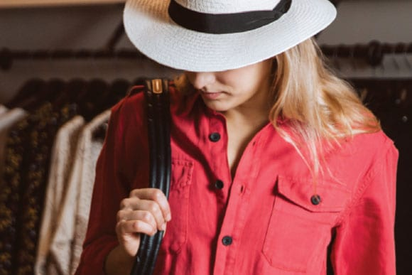 Woman wearing a stylish blouse and hat from Embellish