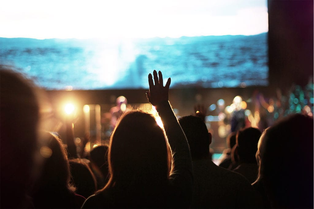 Hands raised in worship as the band is performing