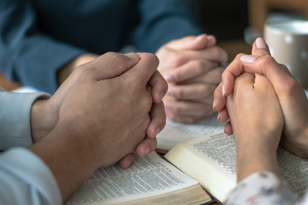 hands folded in prayer on top of Bibles at Biblestudy