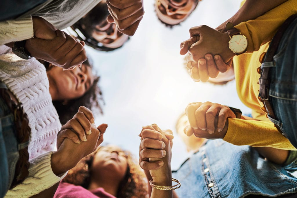 circle of people holding hands as they pray