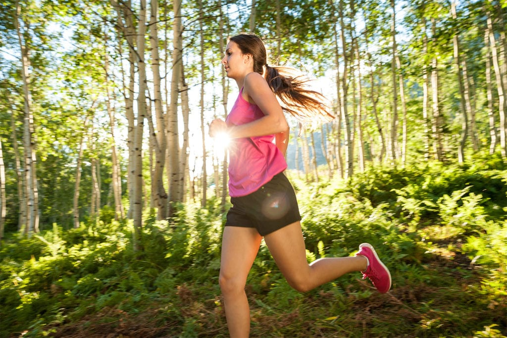 woman running on a wooded trail
