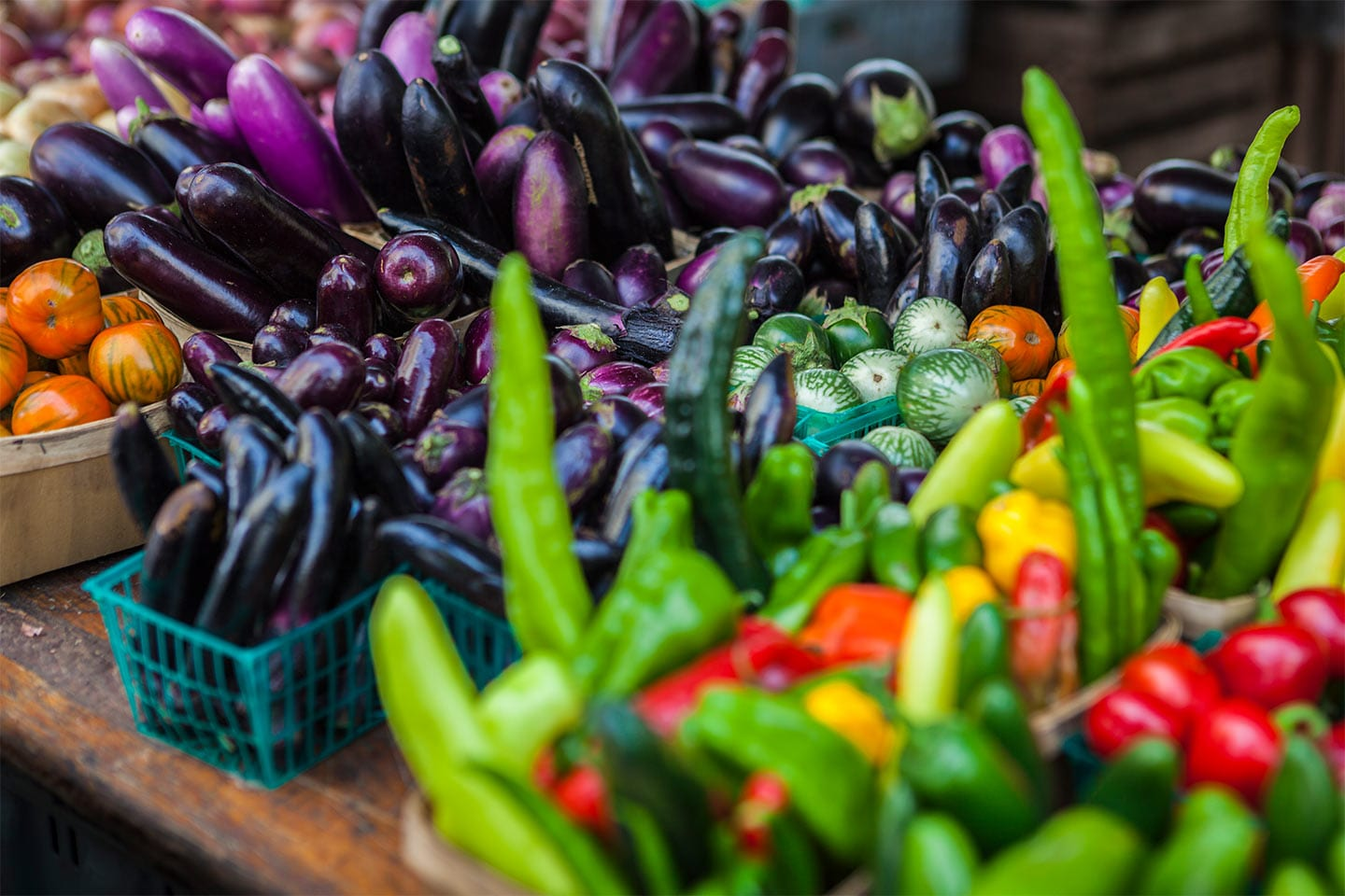 fresh eggplant and peppers and vegetables at a farmers market