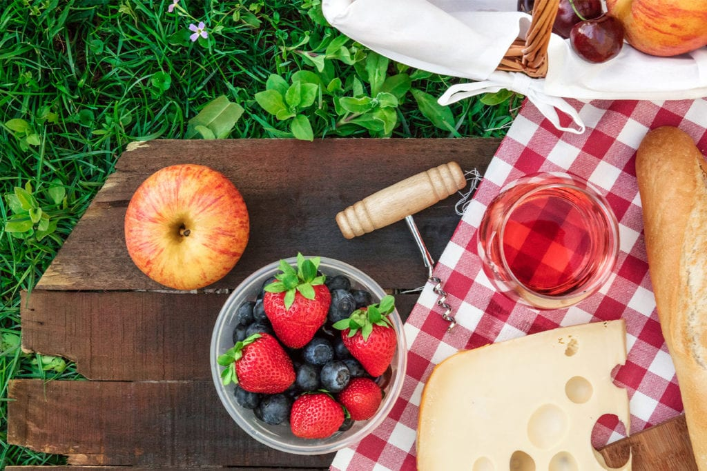 fruit and cheese on a picnic blanket