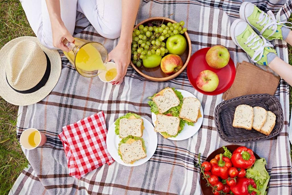 picnic food on blanket with woman pouring juice