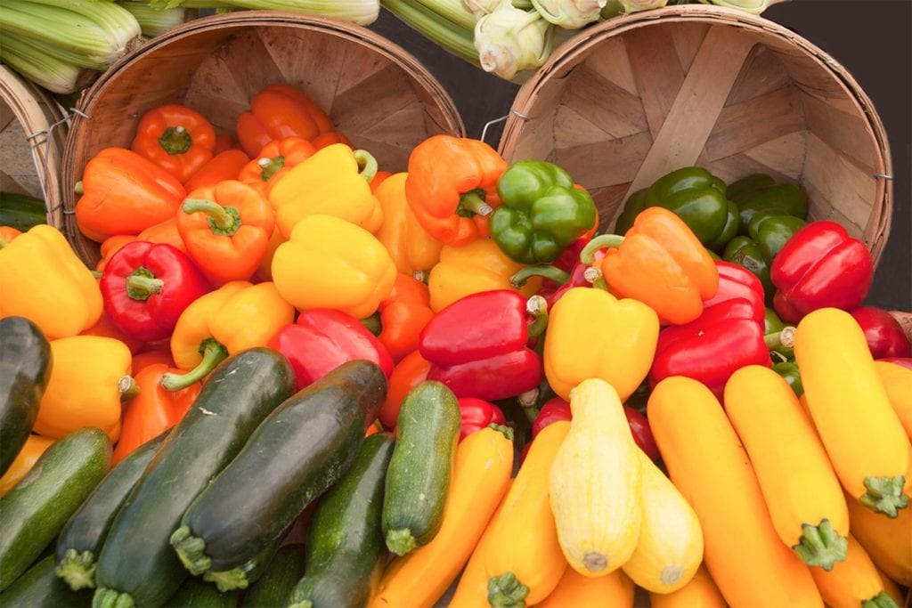 fresh squash and bell peppers at a farmers market