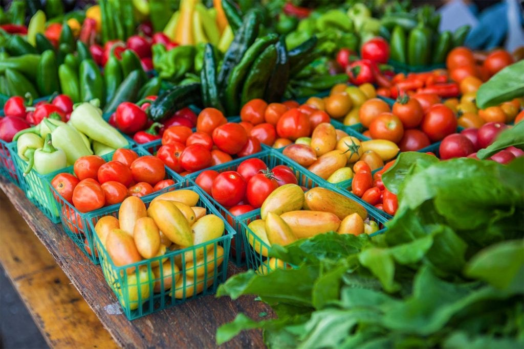 fresh tomatoes and peppers and other produce at a farmers market