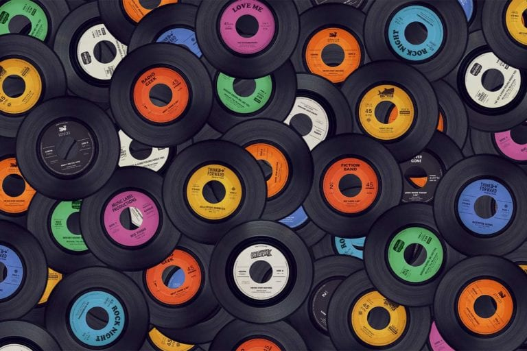 a pile of 45 inch vinyl records with colorful labels