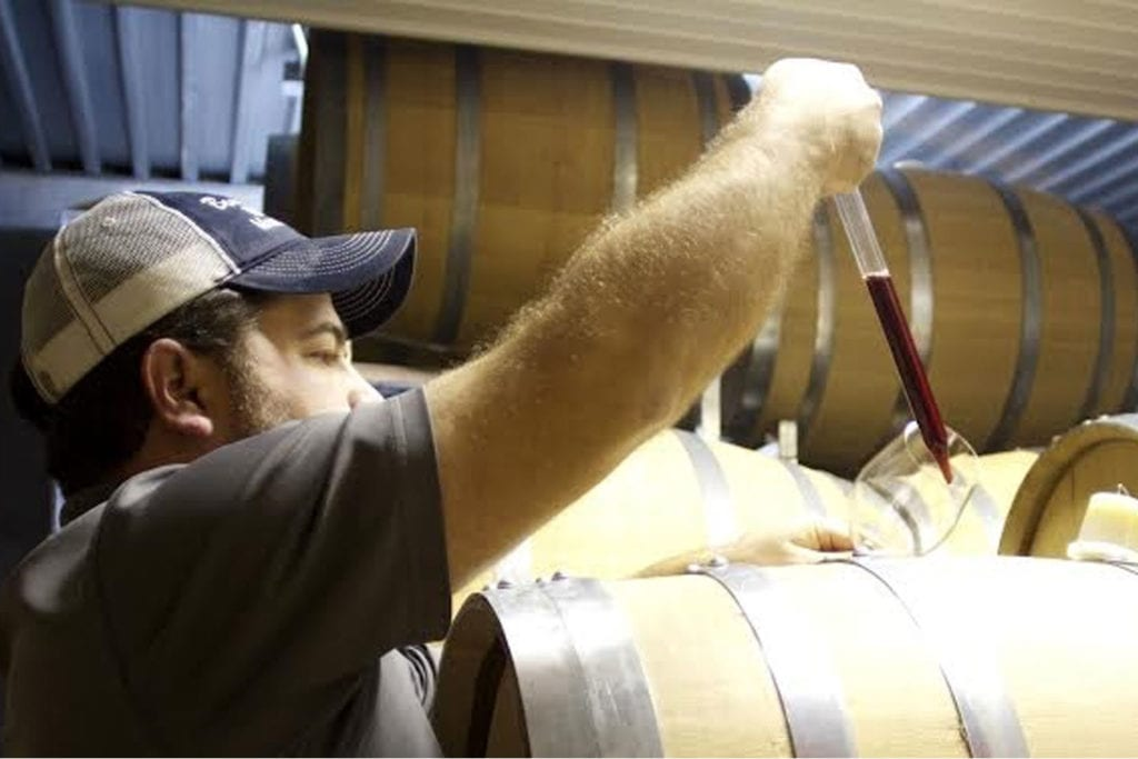 man filling a wine glass from a barrel at Beans Creek Winery; photo courtesy of beans creek winery
