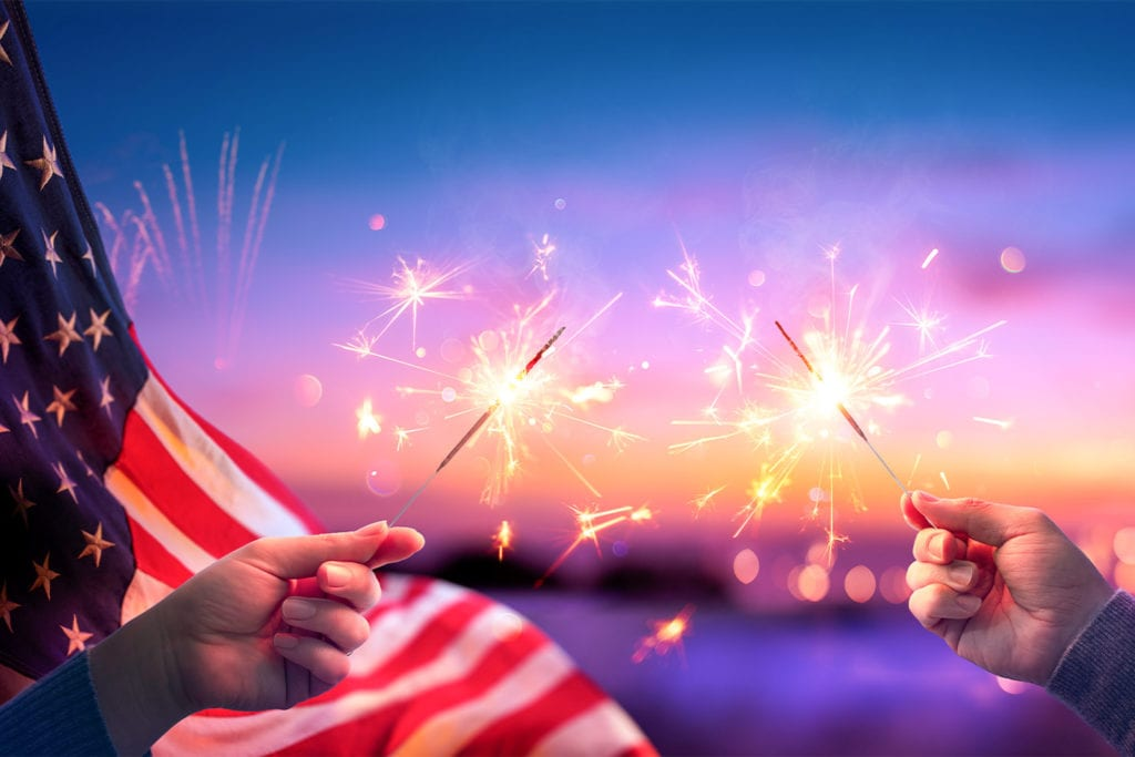 hands holding sparklers with an American flag waving behind them for the fourth of July
