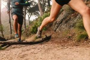 close up shot of people's legs as they are trail running