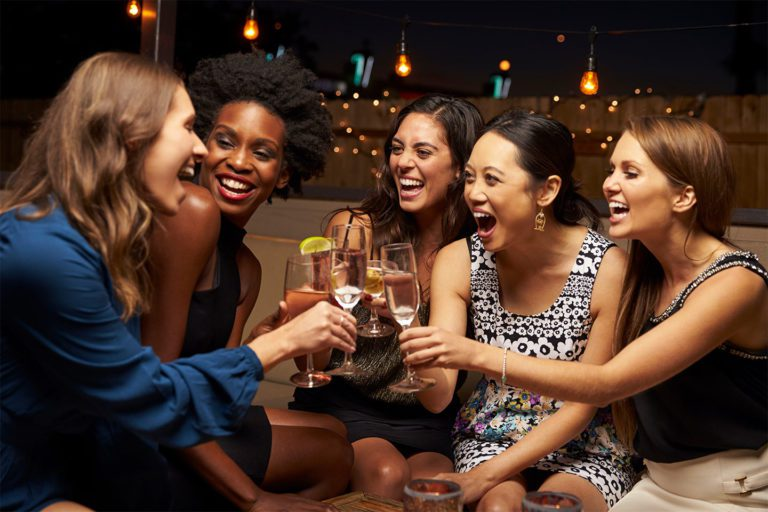 women drinking together at a bar