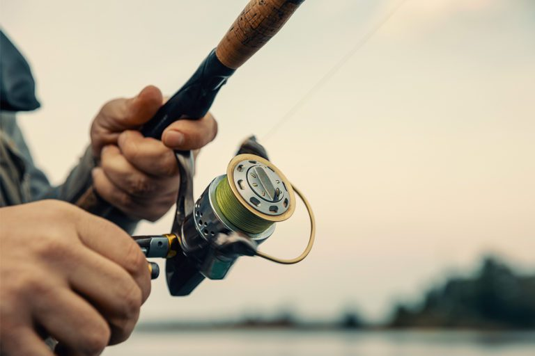 Man's hands holding fishing rod by the lake